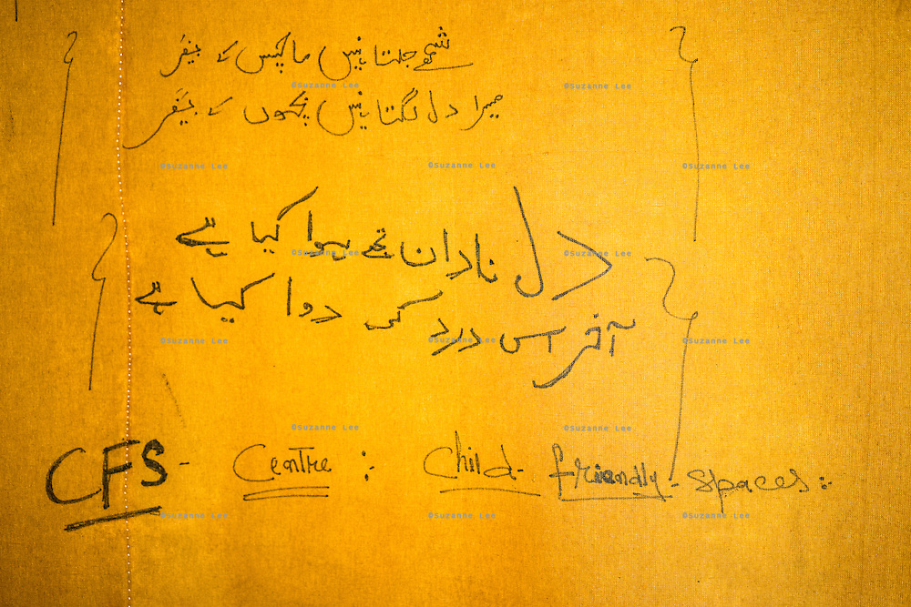 Writings on the inside of the tent wall of the Child-Friendly Space in Purnishadashah village, Jammu and Kashmir, India, on 24th March 2015. Save the Children has set up Child-Friendly Spaces (CFS) in many of the affected villages, providing a tented area where children can take emotional shelter and receive psychological first aid as well as continue their education as their homes and schools are being rebuild. Photo by Suzanne Lee for Save the Children