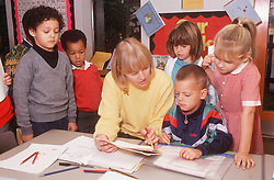 Junior school teacher sitting at table surrounded by multiracial group of children,