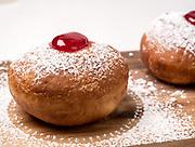 Sufganiyah (sufganiyot) a traditional Jewish Doughnut eaten during Hanukkah with red jam and sugar powder. On white Background