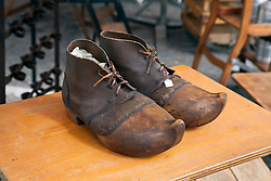 A pair of unusual wood and leather work boots, probably Dutch, await a buyer at a Sunday flea and antiques market in L'Isle-sur-la-Sorgue. Considering its more than 300 permanent antique shops and decorator establishments, this town in Provence is the second largest (after Paris) antiques center in France.   Vintage clothing, toys, and antiques share sidewalk space with amazing food and working artists during the year-round Sunday flea markets for which the town of L'Isle-sur-la-Sorgue also is famous.