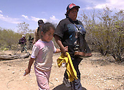 A 6-year-old girl, who crossed in to the U.S. illegally from Mexico, walks with her aunt and other relatives on the Tohono O'odham Nation in Arizona in temperatures exceeding 110 degrees.