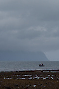 Firsherman on boat under storm clouds in Rescurrection Bay, Seward, Alaska