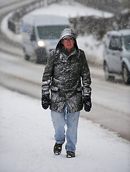 © Licensed to London News Pictures. 13/03/2013..North Yorkshire, England..A man walks through snow in Brotton as heavy snow falls over North Yorkshire as the wintery weather continues...Photo credit : Ian Forsyth/LNP