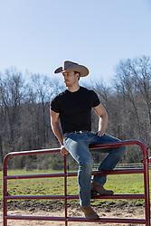 cowboy sitting on a ranch fence