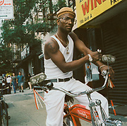 Man on his schwinn bike wearing white jeans and a vest USA