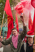 Smoke is released as Members of the Communist Party of Great Britain enter Trafalgar Square - the May Day March from Clerkenwell Green ending with a rally in Trafalgar Square - against cuts and anti 'Trade Union laws. It was supported by several trade unions including UNITE, PCS, ASLEF, RMT, TSSA, NUT, FBU, GMB and UNISON as well as the Peoples Assembly, Pensioners' organisations and organisations representing migrant workers & communities.