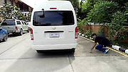 4ft long monitor lizard found hiding in mini van<br /> <br /> This is the moment men use a stick to poke out a monitor lizard hiding underneath a minivan.<br /> <br /> The 4ft long reptile had scampered inside the new white truck while it was parked up in Ayuthaya, central Thailand.<br /> <br /> Eagle-eyed passerby Punlert Insri, 35, spotted the creature's tail hanging down and alerted the driver before the engine started up.<br /> <br /> One man poked a small tree branch through the side of the bus while another coaxed out the reptile from behind with a stick.<br /> <br /> Eventually the adventurous lizard dropped out and tried to make his escape into nearby bushes and over a garden wall.<br /> <br /> But the group of men cornered the critter - a common wild pest in the country - before catching him and moving him into nearby jungle with a lake for it to bathe in.<br /> <br /> Punlert said: ''We didn't want him to get injured when the car started up. So we had to use sticks to get him out of the wheel chassis.<br /> <br /> ''They're not the easiest creatures to catch. They will bite and scratch so we didn't use bare hands. So we had to use sicks.<br /> <br /> ''It's good luck for us if we release a lizard like this back into the wild. We chased him down, caught him and took him to a wild area with a pond.''<br /> Punlert Insri/Exclusivepix Media
