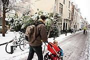 Een man loopt met zijn kind in de wandelwagen door de sneeuw in Utrecht. In grote delen van Nederland is vandaag voor het eerst sneeuw gevallen