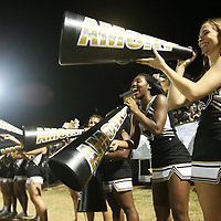 Amory cheerleaders Madison Wax, center right, laughs with Kylee Westbrook, far right, as they cheer on the sidelines during Friday night's game against Aberdeen.