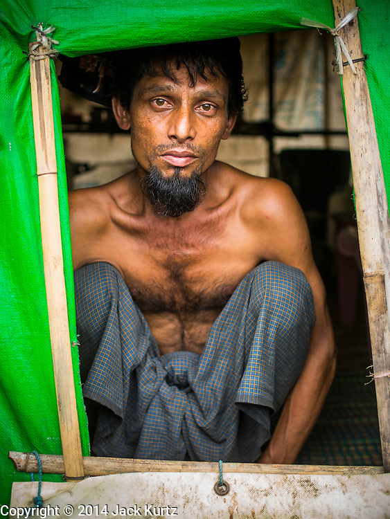 """07 NOVEMBER 2014 - SITTWE, RAKHINE, MYANMAR: A Rohingya Muslim man looks out a """"window"""" of his tent in an IDP camp for Rohingya. After sectarian violence devastated Rohingya communities and left hundreds of Rohingya dead in 2012, the government of Myanmar forced more than 140,000 Rohingya Muslims who used to live in and around Sittwe, Myanmar, into squalid Internal Displaced Persons camps. The government says the Rohingya are not Burmese citizens, that they are illegal immigrants from Bangladesh. The Bangladesh government says the Rohingya are Burmese and the Rohingya insist that they have lived in Burma for generations. The camps are about 20 minutes from Sittwe but the Rohingya who live in the camps are not allowed to leave without government permission. They are not allowed to work outside the camps, they are not allowed to go to Sittwe to use the hospital, go to school or do business. The camps have no electricity. Water is delivered through community wells. There are small schools funded by NOGs in the camps and a few private clinics but medical care is costly and not reliable.   PHOTO BY JACK KURTZ"""