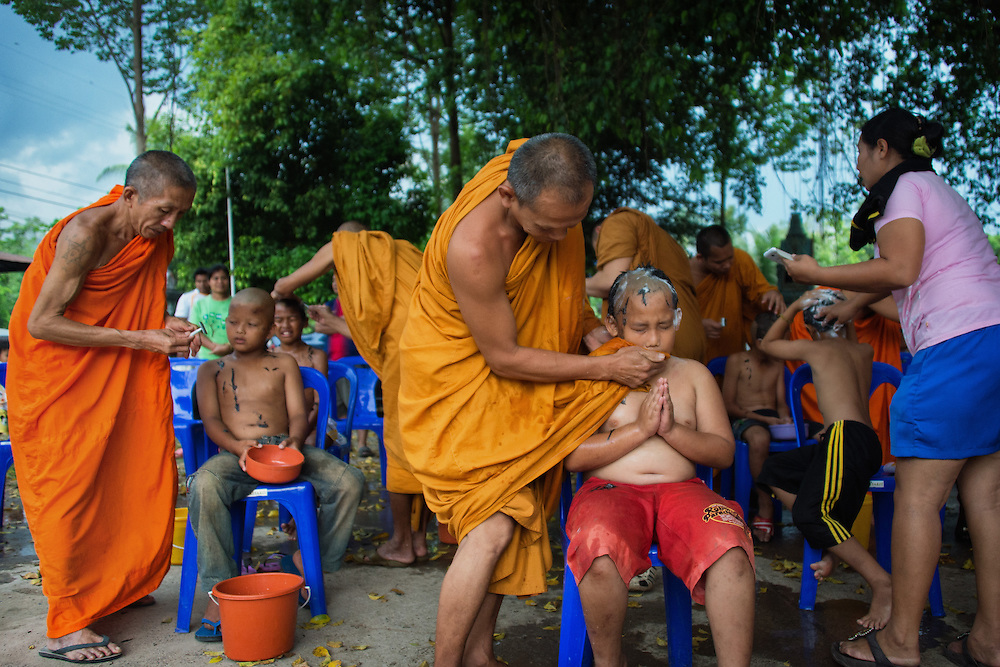 Young men have their heads shaved as they prepare to become novice monks in  rural Nakhon Nayok, Thailand. PHOTO BY LEE CRAKER