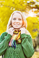 Portrait of Beautiful woman standing and smiling while holding her scarf with lens flare in background