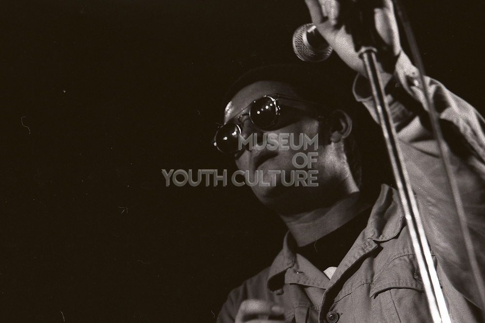 Paul Heaton holding microphone, wearing hat, glasses, and denim jacket, Manchester, UK, circa 1989