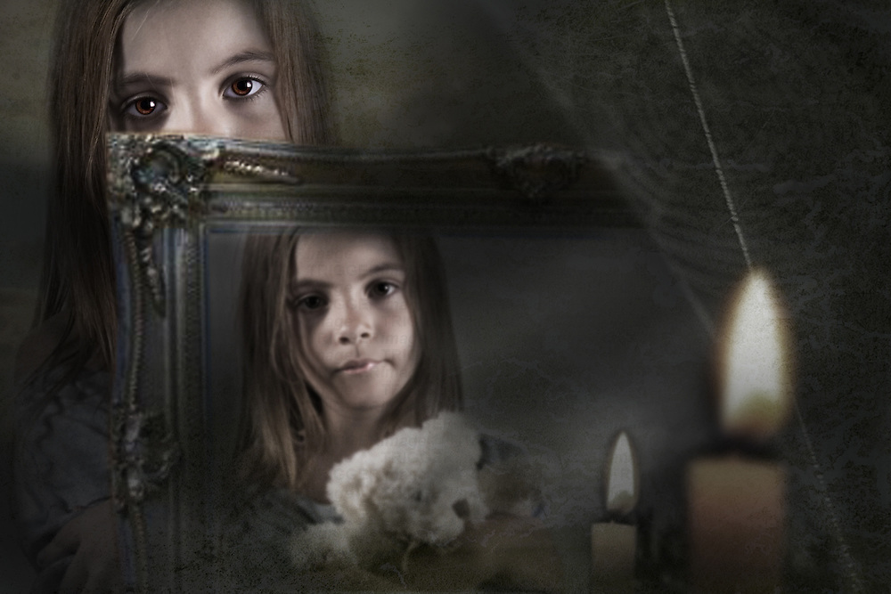 young child reflected in a mirror holding a teddy bear