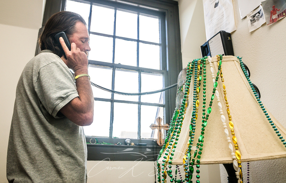 Veteran Darren Dalpiaz answers a phone call from one of his street friends, Nov. 12, 2015, in New Orleans, Louisiana. Dalpiaz, 49, was homeless for 25 years before moving into Sacred Heart Apartments, a community of formerly homeless veterans and non-veterans. UNITY, a 60-agency coalition, provides housing and services for people who are homeless. Dalpiaz was the last of 227 homeless veterans housed by UNITY. (Photo by Carmen K. Sisson/Cloudybright)