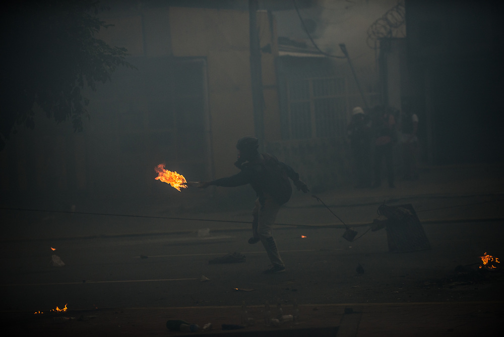 CARACAS, VENEZUELA - MAY 22, 2017:  Anti-government protesters run through a cloud of tear gas to throw rocks and molotov cocktails at security forces, who responded by heavily tear gassing and firing rubber bullets and buckshot at them.  The streets of Caracas and other cities across Venezuela have been filled with tens of thousands of demonstrators for nearly 100 days of massive protests, held since April 1st. Protesters are enraged at the government for becoming an increasingly repressive, authoritarian regime that has delayed elections, used armed government loyalist to threaten dissidents, called for the Constitution to be re-written to favor them, jailed and tortured protesters and members of the political opposition, and whose corruption and failed economic policy has caused the current economic crisis that has led to widespread food and medicine shortages across the country.  Independent local media report nearly 100 people have been killed during protests and protest-related riots and looting.  The government currently only officially reports 75 deaths.  Over 2,000 people have been injured, and over 3,000 protesters have been detained by authorities.  PHOTO: Meridith Kohut