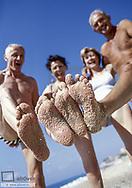 Zwei Seniorenpaare an Strand, Sand an Fuessen (model-released)