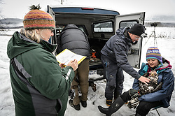 "Dr. Scott Ford, avian veterinarian, Avian Speciality Veterinary Services of Alaska, comforts a bald eagle (Haliaeetus leucocephalus) captured in the Alaska Chilkat Bald Eagle Preserve. Ford was assisting Steve Lewis, Raptor Management Coordinator, U.S. Fish & Wildlife Service (back to camera) and Rachel Wheat, graduate student at the University of California Santa Cruz (not pictured), in the processing of eagles Wheat is studying. Wheat is conducting a bald eagle migration study of eagles that visit the Chilkat River for her doctoral dissertation. She hopes to learn how closely eagles track salmon availability across time and space. The bald eagles are being tracked using solar-powered GPS satellite transmitters (also known as a PTT - platform transmitter terminal) that attach to the backs of the eagles using a lightweight harness. Holding the eagle is Yiwei Wang, graduate student, University of California Santa Cruz. Helping with the recording of measurements taken of the bald eagle is Pam Randles, Takshanuk Watershed Council Education Director (left). The latest tracking location data of this bald eagle known as ""2Z"" can be found here: http://www.ecologyalaska.com/eagle-tracker/2z/ . During late fall, bald eagles congregate along the Chilkat River to feed on salmon. This gathering of bald eagles in the Alaska Chilkat Bald Eagle Preserve is believed to be one of the largest gatherings of bald eagles in the world."