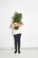 Woman holding potted orange tree over face