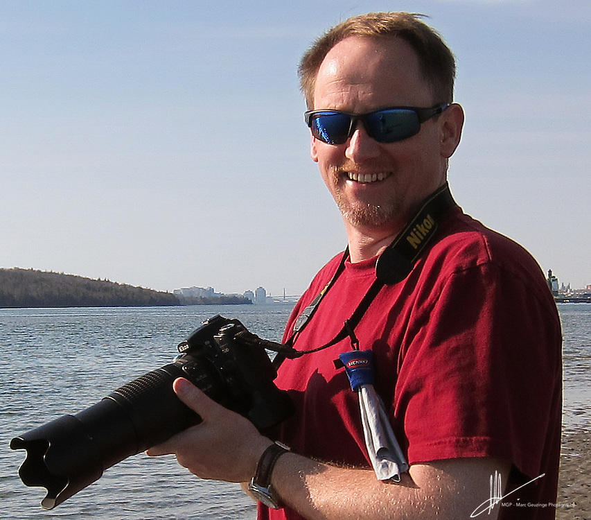 Marc Geuzinge holding a Nikon camera in Eastern Passage , Nova Scotia. Marc Geuzinge is the owner and photographer of Marc Geuzinge Photography