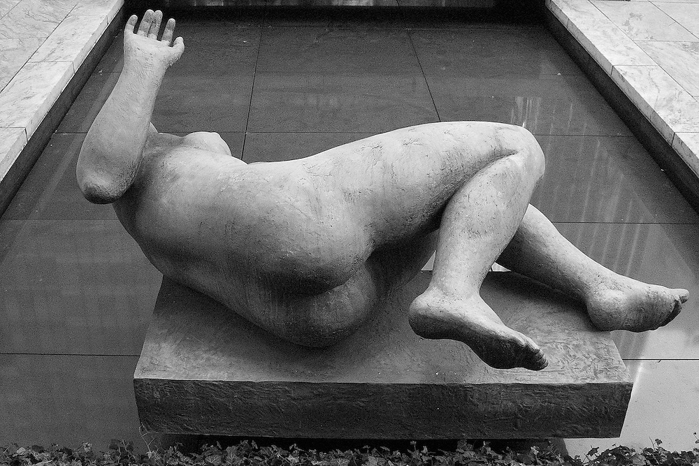 "A black and white photograph of Aristede Maillol's ""The River"" in the Sculpture Garden at the Museum of Modern Art in New York City."