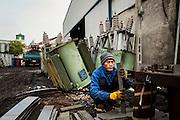 A Vietnamese man squats as he organizes recycled metal plates in Man Xa Village.  Northern outskirts of Hanoi, Vietnam, Southeast Asia