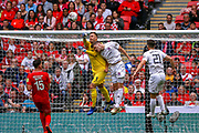 AFC Flyde defender Jordan Tunnicliffe (5) and Leyton Orient goalkeeper Dean Brill (1) clash in the air during the FA Trophy final match between AFC Flyde and Leyton Orient at Wembley Stadium on 19 May 2019.