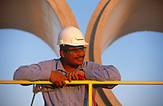 "A Mexican-born employee of Hanson Pipe & Products, at Grand Prairie, Texas, USA...They are inspcting the inner-surfaces and tongue and groove seals of the horizontal pipes wearing obligatory hard hats and corporate blue shirts. Precast concrete is made from a reusable mold or ""form"" and cured in a controlled environment, then transported to the construction site and lifted into place. Used in the construction of commercial building components, bridges, manholes and retaining walls, these products are the strongest pipe available, designed and plant tested to resist any load required with a design life of 70-100 years. ..."