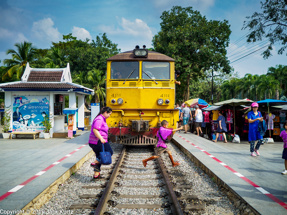 """09 JANUARY 2019 - KANCHANABURI, THAILAND: Thai students on a school field trip run in front of a train stopped in the station at the """"Bridge On the River Kwai"""" in Kanchanaburi. Hundreds of thousands of Asian slave laborers and Allied prisoners of war died in World War II constructing the """"Death Railway"""" between Bangkok and Rangoon (now Yangon), Burma (now Myanmar) for the Japanese during World War II.  The bridge is now one of the most famous tourist attractions in Thailand.     PHOTO BY JACK KURTZ"""