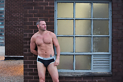 middle aged man in calvin klein briefs leaning against a brick wall and window on a rooftop in New York City