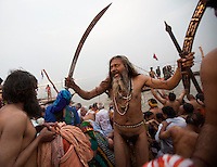 A Naga sadhu (naked holy man) has just bathed in the holy Ganga. The sadhu are solely dedicated to achieving liberation, the fourth and final stage of life, through meditation and contemplation. It is said that the sword and other weapons carried by these men reinforce the belief that the Naga sadhus are the protectors of ancient culture and Hindu dharma. They are considered precious jewels for the Naga sadhus.