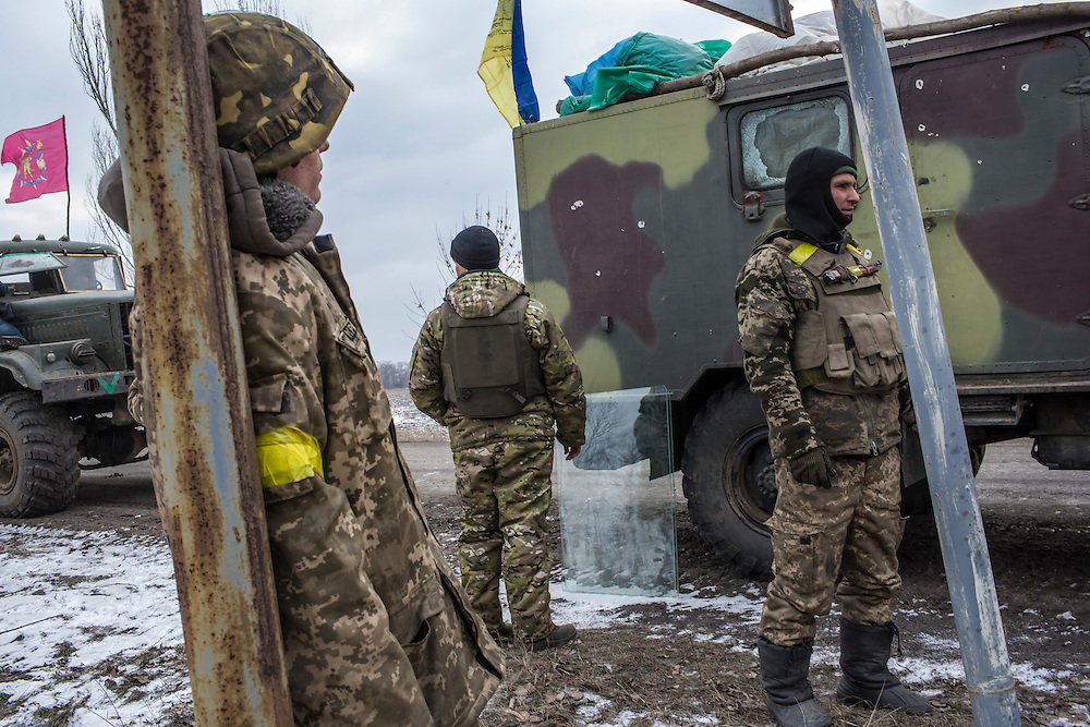 ARTEMIVSK, UKRAINE - FEBRUARY 19: Ukrainian soldiers from a unit based in Zaporizhia relax by the roadside after leaving Debaltseve on February 19, 2015 in Artemivsk, Ukraine. Ukrainian forces started withdrawing from the strategic and hard-fought town of Debaltseve yesterday being effectively surrounded by pro-Russian rebels. (Photo by Brendan Hoffman/Getty Images) *** Local Caption ***