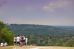 © Licensed to London News Pictures. 12/08/2020. Surrey, UK. Calm before the storms. Walkers look at the dramatic thunder clouds as they loom over Box Hill in Surrey as the tropical heatwave continues to hit England with temperatures in excess of 34c today. Weather forecasters have predicted that thunderstorms with heavy rain are likely to hit Surrey and London later tonight with the Met Office issuing a yellow weather warning for thunderstorms in the South East of England with risk of flooding and travel disruption. Photo credit: Alex Lentati/LNP
