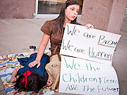 14 MARCH 2011 - PHOENIX, AZ: A girl and her sister rest during an immigration protest at the Arizona State Capitol in Phoenix Monday. Protests by immigrants' rights activists have continued as the state's conservative Republican legislators debate toughening the state's anti-immigrant bills. Some of the bills the state legislature has debated this year include eliminating birthright citizenship, a law that would require hospitals to check the immigration status of patients checking in for elective care, a bill that would require schools to verify the immigration status of students when they enroll and a bill that would require law enforcement to impound the cars of undocumented immigrants even if they have a legal driver's license from another state.      Photo by Jack Kurtz