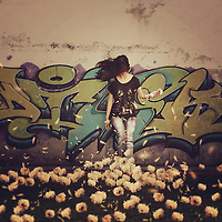 conceptual artwork of a girl in front of a graffiti wall and a field of white flowers