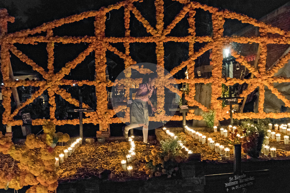 A young girl walks along a decorated gravesite during the Day of the Dead festival October 31, 2017 in Tzintzuntzan, Michoacan, Mexico.