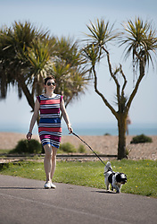 © Licensed to London News Pictures. 05/05/2018. Worthing, UK. A woman walks her dog on the sea front at Worthing in the sunshine. Record temperatures are expected this bank holiday weekend. Photo credit: Peter Macdiarmid/LNP