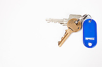 Keys with blue key ring tag on white background