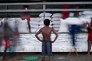 Labour workers on the riverbank of the Ayeyarwaddy unloading boats, Mandalay, Myanmar