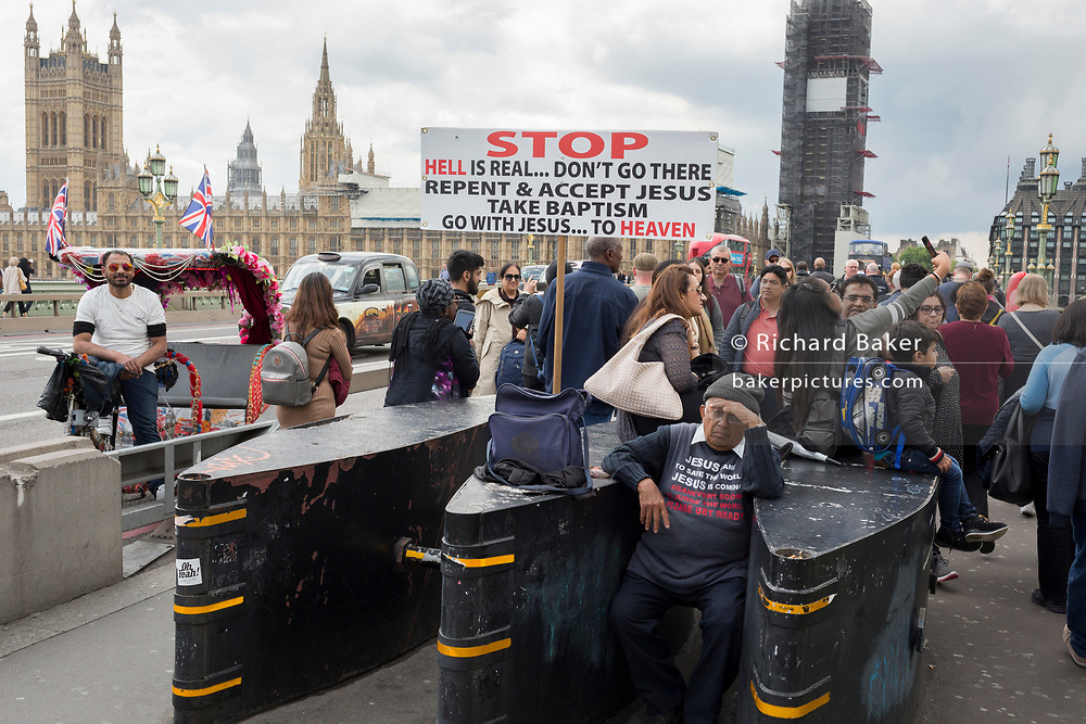 With the Houses of Parliament in the background, a Christian gentleman looks weary among tourist crowds on the southern end of Westminster Bridge, on 11th June 2019, in London, England.