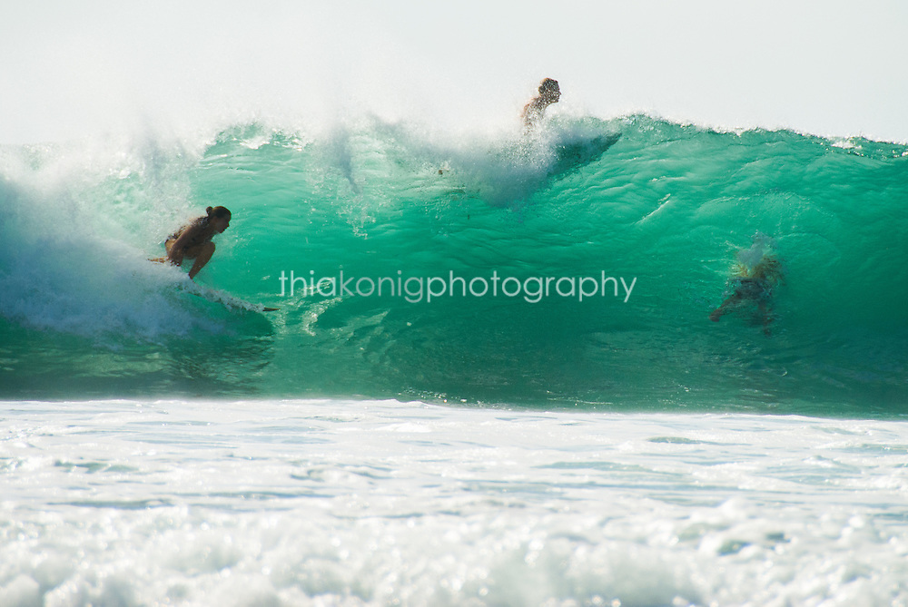 A female surfer takes off on a translucent aqua blue wave, ghosts of other surfers are visble through the wave.