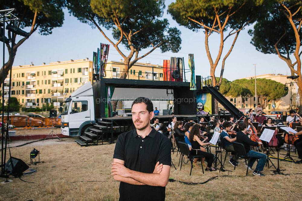 ROME, ITALY - 27 JUNE 2017: Director Fabio Cherstich poses for a portrait by the truck of the &quot;Don Giovanni OperaCamion&quot;, an open-air opera performed on a truck during the orchestra rehearsal in San Basilio, a suburb in Rome, Italy, on June 27th 2017.<br /> <br /> Director Fabio Cherstich&rsquo;s idae of an &ldquo;opera truck&rdquo; was conceived as a way of bringing the musical theatre to a new, mixed, non elitist public, and have it perceived as a moment of cultural sharing, intelligent entertainment and no longer as an inaccessible and costly event. The truck becomes a stage that goes from square to square with its orchestra and its company of singers in Rome. <br /> <br /> &ldquo;Don Giovanni Opera Camion&rdquo;, after &ldquo;Don Giovanni&rdquo; by Wolfgang Amadeus Mozart is a new production by the Teatro dell&rsquo;Opera di Roma, conceived and directed by Fabio Cherstich. Set, videos and costumes by Gianluigi Toccafondo. The Youth Orchestra of the Teatro dell&rsquo;Opera di Roma is conducted by Carlo Donadio.