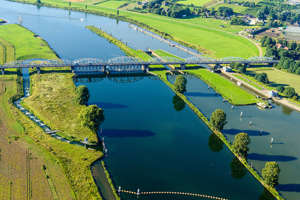 Nederland, Noord-Brabant, Grave, 23-08-2016; stuw in de rivier de Maas, dient om de waterloop te reguleren en het peil te beheren. Naast de stuw de schutsluis voor de scheepvaart en de  vistrap waardoor de vissen langs de stuw stroomopwaarts kunnen zwemmen. De vakwerkbrug is voor de lokaal verkeer over de rivier.<br /> Flood barrier in the river Meuse to regulate the watercours and manage the water level<br /> Next to the barrier the lock for barges and the newly built 'fish stairway' (which alows fish to pass the barrier). The lattice bridge is for the local road over the river<br /> aerial photo (additional fee required); <br /> luchtfoto (toeslag op standard tarieven);<br /> copyright foto/photo Siebe Swart