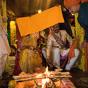 A sacred fire is lit and amidst Vedic chantings, the groom's shawl is tied to the bride's 'duppata' or veil, and the couple goes around the fire seven times. Each circle around the fire is known as a 'phera'. A Rajput wedding in India
