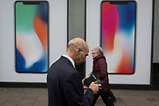 A man uses his handset while walking past an ad for the new Apple iPhone X outside a branch of Carphone Warehouse, on 22nd November 2017, in London England.
