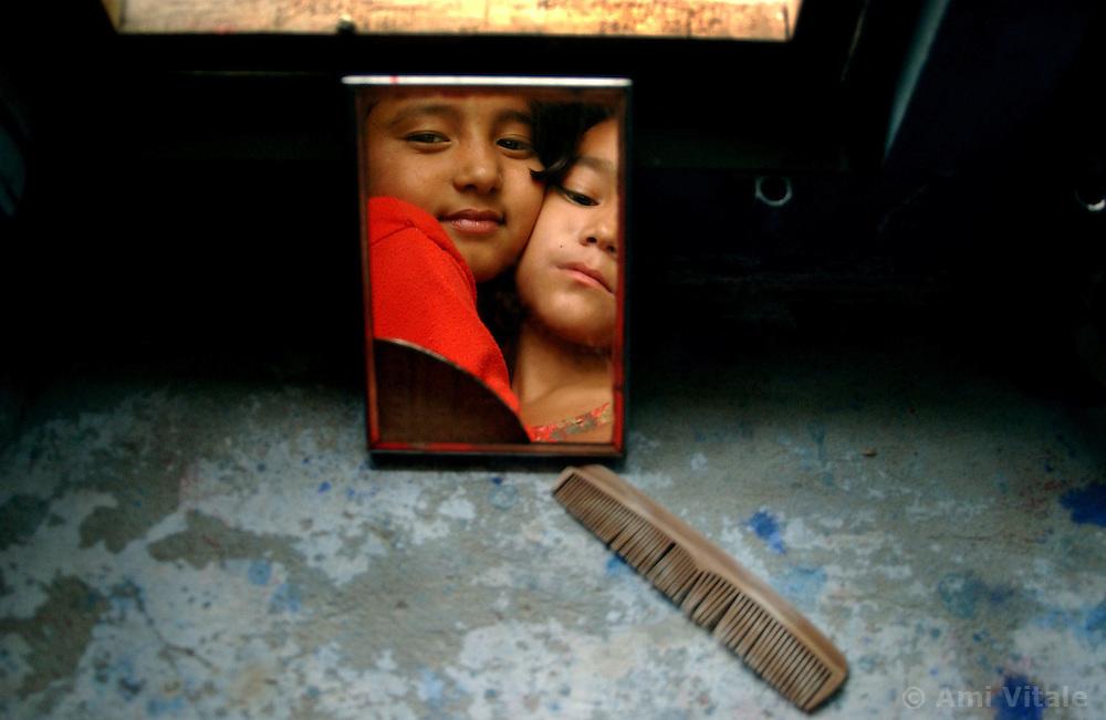 NEPALGANJ, NEPAL, APRIL 14, 2004: Nepali girls orphaned because of the Maoist insurgency hug eachother as they play inside the Sahara orphanage in Nepalganj, Nepal April 14, 2004.   (Ami Vitale/Getty Images)