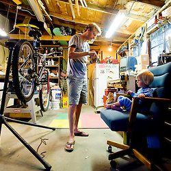 060811       Brian Leddy.Dirk Hollebeek works on a bike with his daughter Olivia at their home on Tuesday. Hollebeek, who runs the Gallup Bicycle District business out of his home, has been wrenching on bikes for the past two months.