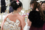 two young adult girls one in kimono other in modern clothing at a wedding celebration Japan