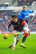 Ryan Kent (#14) of Rangers FC challenges Aaron Hickey (#51) of Heart of Midlothian FC during the Ladbrokes Scottish Premiership match between Rangers FC and Heart of Midlothian FC at Ibrox Park, Glasgow, Scotland on 1 December 2019.