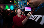 "Sayta Rhodes-Conway celebrates her victory over incumbent Paul Soglin by signing the ""Satya"" sticker of security guard Jeff Thompson during the Madison Mayoral Election watch party at Prism Dance Club in Madison, WI on April 2, 2019."
